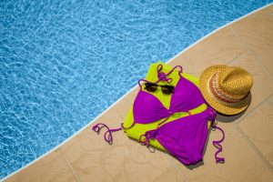 Purple bikini, lime green beach towel, sunglasses and hat by swimming pool.